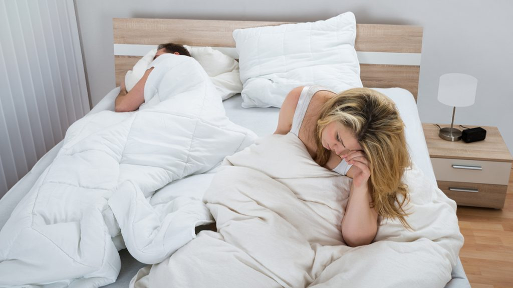 Unhappy Woman With Blanket On Bed While Man Sleeping In Bedroom
