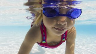 underwater lifestyle shot of a female toddler in goggles as she learns to swim in a pool