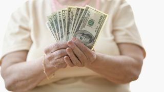 Close-up of a senior woman holding paper currency