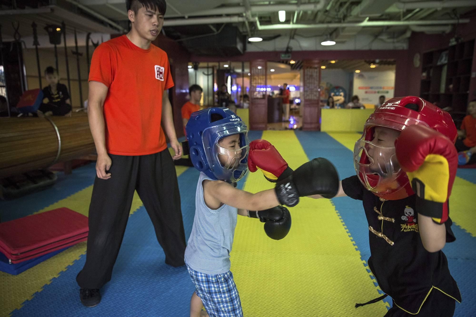 Peking, 2017. szeptember 8.Párosgyakorlatot végeznek oktatójuk jelenlétében egy kungfuiskola fiatal növendékei a pekingi bevásárlóközpontok egyikében működő tanodájukban 2017. július 22-én. (MTI/EPA/Roman Pilipej)