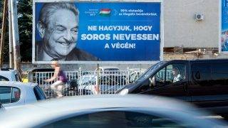 """A poster with US billionaire George Soros is pictured on July 6, 2017 in Szekesfehervar, Hungary.The head of Hungary's largest Jewish organisation says a """"poisonous"""" poster campaign by the government that targets US billionaire George Soros is stoking anti-Semitic sentiments and urged its immediate scrapping. / AFP PHOTO / ATTILA KISBENEDEK / TO GO WITH AFP STORY"""