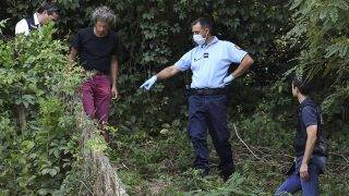 French gendarmes search for evidence around the garden of a man near Pont-de-Beauvoisin, eastern france, on August 30, 2017 after the disappearance of a 9-year-old girl.