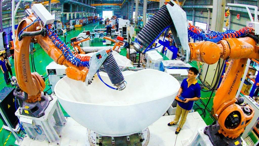 --FILE--A Chinese worker tests robot arms for glazing bathroom products at the plant of Foshan LXD Robotics Co., Ltd. in Foshan city, south China's Guangdong province, 7 May 2015.