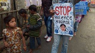 Street children look on as Indian social activists take part in a rally on the International Day for the Elimination of Violence against Women in Kolkata on November 25, 2013. The activists pledged to wage a struggle against all forms of violence against women. India has become hugely sensitive to gender issues since the fatal gangrape of a student in New Delhi last December stirred nationwide protests about violence to women and prompted calls for profound changes in social attitudes. AFP PHOTO/Dibyangshu SARKAR / AFP PHOTO / DIBYANGSHU SARKAR