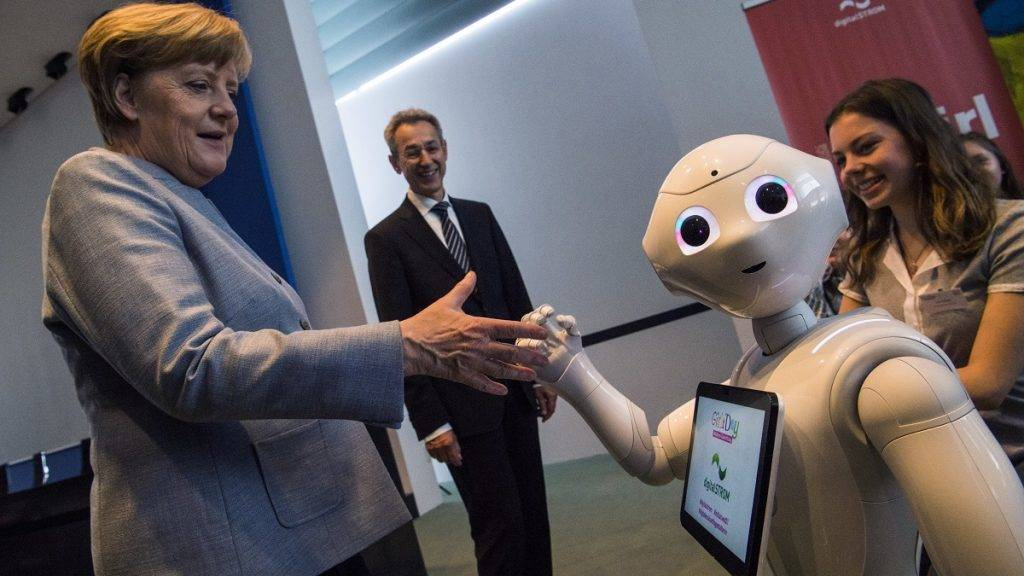 German Chancellor Angela Merkel greets an interactive robot at the digitalSTROM stand during the annual Girl's Day fair at the chancellery in Berlin on April 26, 2017. The fair aims to attract young women to hi-tech and engineering jobs.  / AFP PHOTO / John MACDOUGALL