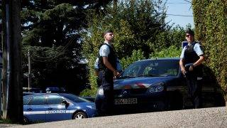 French gendarmes stand next to their vehicles in front of the house of a man charged with kidnapping following the disapperance of a nine-year-old girl, as the house is being searched on September 5, 2017 in Domessin, near the southeastern village of Pont-de-Beauvoisin. The 34-year-old local man charged with kidnapping Maelys de Araujo, who went missing during a wedding in the Alps, has admitted she got into his car but denies abducting her, his lawyer said. The DNA was found mixed in with that of the driver on the dashboard of the vehicle, which was parked next to the venue and was cleaned the day after the celebrations. / AFP PHOTO / JEFF PACHOUD