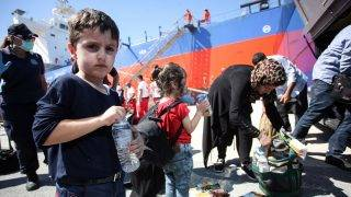 Migrants receive food and water after disembarking from a vessel at the port of Heraklion on the island of Crete on September 5, 2017, after being rescued off the coast of the Greek island.  A group of some 103 migrants aboard a wooden boat off the islands' eastern coast have been safely transferred to the port, with the last few days seeing an increase in refugees and migrant arrivals in Greece.  / AFP PHOTO / COSTAS METAXAKIS