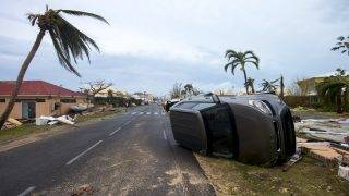 A photo taken on September 6, 2017 shows a car turned onto its side in Marigot, near the Bay of Nettle, on the French Collectivity of Saint Martin, after the passage of Hurricane Irma. France, the Netherlands and Britain on September 7 sent water, emergency rations and rescue teams to their stricken territories in the Caribbean hit by Hurricane Irma, which has killed at least 10 people. The worst-affected island so far is Saint Martin, which is divided between the Netherlands and France, where eight of the 10 confirmed deaths took place.  / AFP PHOTO / Lionel CHAMOISEAU