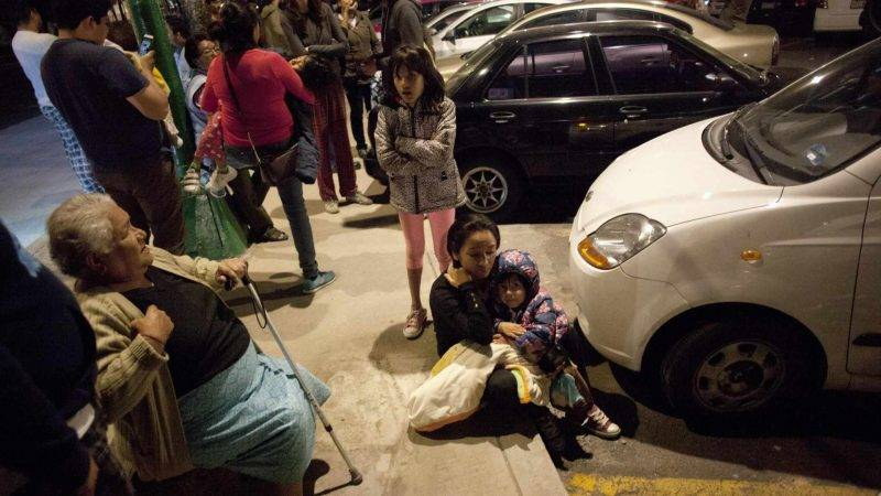 People react on a street in downtown Mexico City during an earthquake on September 7, 2017. An earthquake of magnitude 8.0 struck southern Mexico late Thursday and was felt as far away as Mexico City, the US Geological Survey said, issuing a tsunami warning. It hit offshore 120 kilometers (75 miles) southwest of the town of Tres Picos in the state of Chiapas.   / AFP PHOTO / PEDRO PARDO