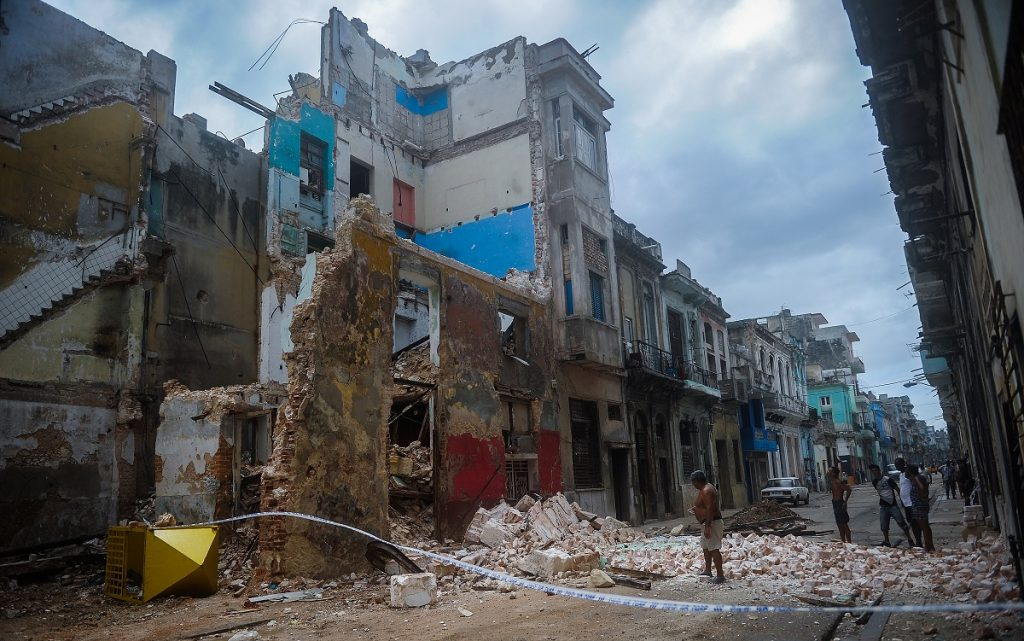 Cubans stand bt a collapsed building in Havana, on September 9, 2017.  Irma's blast through the Cuban coastline weakened the storm to a Category Three, but it is still packing 125 mile-an-hour winds (205 kilometer per hour) and was expected to regain power before hitting the Florida Keys early Sunday, US forecasters said. The Cuban government extended its maximum state of alert to three additional provinces, including Havana, amid fears of flooding in low-lying areas. / AFP PHOTO / YAMIL LAGE