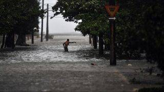 A man wades through a flooded street during the passage of Hurricane Irma, in Havana, on September 9, 2017.  Irma's blast through the Cuban coastline weakened it to a Category Three, but it is still packing winds of 125 miles (200 kilometer) per hour. / AFP PHOTO / YAMIL LAGE