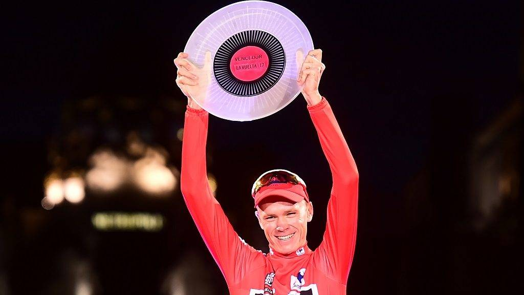 "Team Sky's British cyclist Chris Froome raises his trophy as he celebrates on the podium winning the 72nd edition of ""La Vuelta"" Tour of Spain cycling race, in Madrid, on September 10, 2017. Chris Froome became just the third rider in history to win the Vuelta a Espana and Tour de France in the same year as Matteo Trentin won the 21st stage of the Vuelta through the centre on Madrid on Sunday. / AFP PHOTO / JOSE JORDAN"