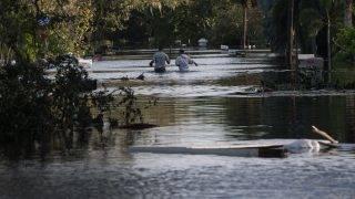People wade through a flooded neighborhood in Bonita Springs, Florida, northeast of Naples, on September 11, 2017, after Hurricane Irma hit Florida. / AFP PHOTO / NICHOLAS KAMM