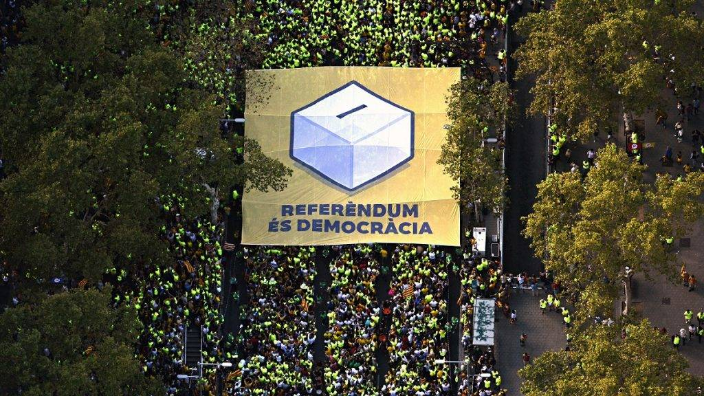 """This handout picture released on September 11, 2017 by the Assemblea Nacional Catalana (Catalan National Assembly) shows an aerial view of people carrying a giant banner depicting a ballot box and reading in Catalan """"Referendum is democracy"""" during a pro-independence demonstration, on September 11, 2017 in Barcelona during the National Day of Catalonia, the """"Diada."""" Hundreds of thousands of Catalans were expected to rally to demand their region break away from Spain, in a show of strength three weeks ahead of a secession referendum banned by Madrid. The protest coincides with Catalonia's national day, the """"Diada,"""" which commemorates the fall of Barcelona in the War of the Spanish Succession in 1714 and the region's subsequent loss of institutions and freedoms.  / AFP PHOTO / ASSEMBLEA NACIONAL CATALANA / ROSER VILALLONGA / RESTRICTED TO EDITORIAL USE - MANDATORY CREDIT """"AFP PHOTO/ ROSER VILALLONGA/ HANDOUT ASSEMBLEA NACIONAL CATALANA"""" - NO MARKETING NO ADVERTISING CAMPAIGNS - DISTRIBUTED AS A SERVICE TO CLIENTS"""