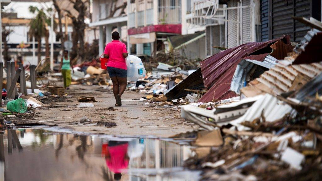 A woman walks on a street in Marigot, on September 11, 2017 on the French Caribbean island of Saint-Martin after it was hit by Hurricane Irma. / AFP PHOTO / Martin BUREAU