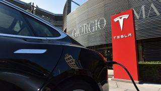 A Tesla car charges at a Tesla charging station outside a shopping mall in Beijing on September 12, 2017.  China is gearing up to ban petrol and diesel cars, a move that would boost electric vehicles and shake up the auto industry in the world's biggest but pollution-plagued market. The plan would follow decisions by France and Britain to outlaw the sale of such cars and vans from 2040 to clamp down on harmful emissions. / AFP PHOTO / GREG BAKER