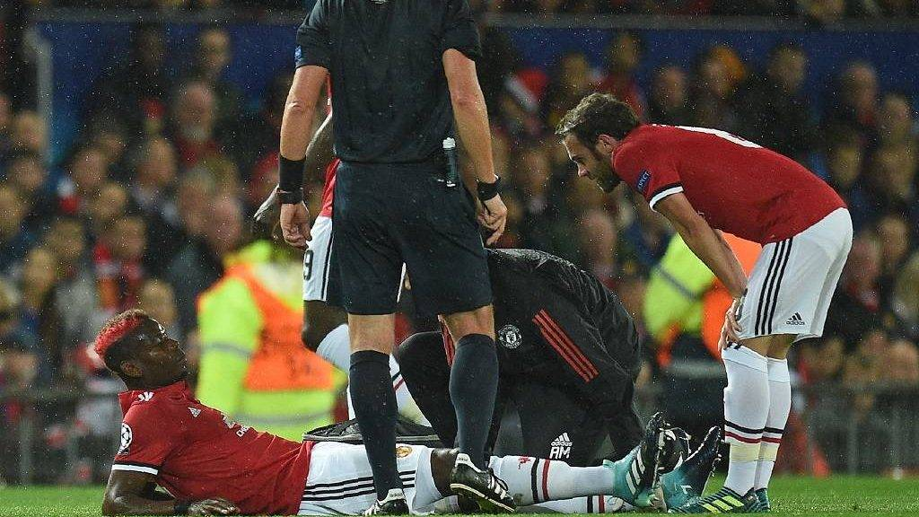 Manchester United's French midfielder Paul Pogba receives medical treatment during the UEFA Champions League Group A football match between Manchester United and Basel at Old Trafford in Manchester, north west England on September 12, 2017. / AFP PHOTO / Oli SCARFF