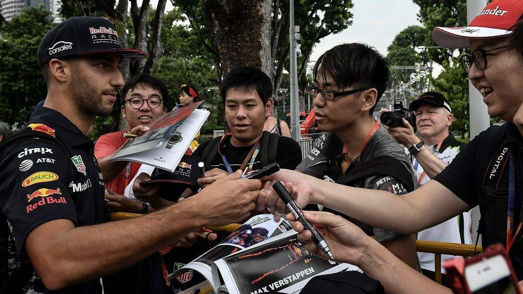 Red Bull's Australian driver Daniel Ricciardo (L) signs autographs as he arrives for the first practice session of the Formula One Singapore Grand Prix in Singapore on September 15, 2017.  / AFP PHOTO / MOHD RASFAN