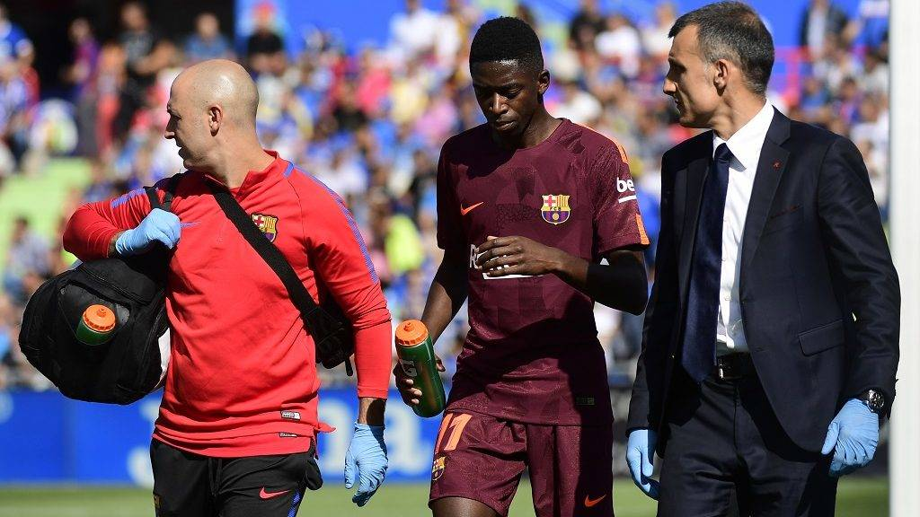 Barcelona's forward from France Ousmane Dembele (C) walks with the team's doctor during the Spanish league football match Getafe CF vs FC Barcelona at the Col. Alfonso Perez stadium in Getafe on September 16, 2017. / AFP PHOTO / PIERRE-PHILIPPE MARCOU