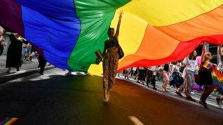 A woman dances under a huge rainbow flag during the Gay Pride parade on September 17, 2017 in Belgrade.  Serbia's lesbian prime minister on September 17 joined hundreds of activists with rainbow flags for Belgrade's annual gay pride march, an event held under heavy security in the conservative country. Belgrade's first Pride march, in 2001, ended with police firing in the air to disperse anti-gay nationalists and skinheads who stoned and beat participants.  / AFP PHOTO / ANDREJ ISAKOVIC