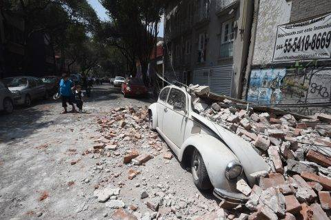 Picture of a car crashed by debris from a damaged building after a quake rattled Mexico City on September 19, 2017. A powerful earthquake shook Mexico City on Tuesday, causing panic among the megalopolis' 20 million inhabitants on the 32nd anniversary of a devastating 1985 quake. The US Geological Survey put the quake's magnitude at 7.1 while Mexico's Seismological Institute said it measured 6.8 on its scale. The institute said the quake's epicenter was seven kilometers west of Chiautla de Tapia, in the neighboring state of Puebla.  / AFP PHOTO / Alfredo ESTRELLA