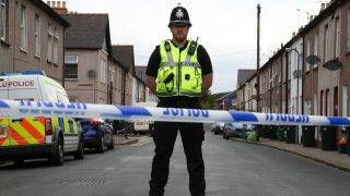 A police officer stands guard at a police cordon near to a house in Newport, south Wales, on September 20, 2017, as they continue their investigations into the September 15 terror attack on a London underground tube train carriage attack at Parsons Green station. Two men were arrested in Wales on Wednesday over last week's London Underground terror attack in which 30 people were injured, bringing the total number of people in custody to five, police said. The men, aged 48 and 30, were arrested under anti-terrorism legislation in Newport in Wales, police said, after a 25-year-old man was arrested in the same city on Tuesday. / AFP PHOTO / GEOFF CADDICK