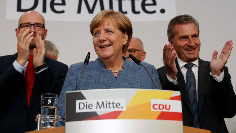 German Chancellor and CDU party leader Angela Merkel (C) addresses supporters after exit poll results were broadcasted on public television at an election night event at the party's headquarters in Berlin during the general election on September 24, 2017.Germany voted in a general election expected to hand Chancellor Angela Merkel a fourth term, while the hard-right Alternative for Germany (AfD) party is predicted to win its first seats in the national parliament. / AFP PHOTO / Odd ANDERSEN