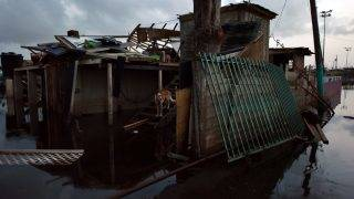 A dog is seen during the nightfall at a house destroyed by the passage of Hurricane Maria in Juana Matos, Catano, Puerto Rico, on September 26, 2017. The US island territory, working without electricity, is struggling to dig out and clean up from its disastrous brush with the hurricane, blamed for at least 33 deaths across the Caribbean. / AFP PHOTO / HECTOR RETAMAL