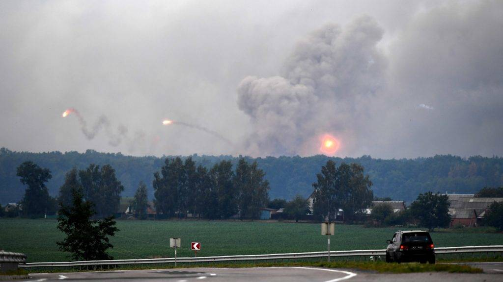 "A car passes while munitions explode at a military depot on September 27, 2017 near Kalynivka.  Ukranian authorities evacuated nearly 30,000 people September 27 from the central Vinnytsya region after a huge munitions depot caught fire and set off artillery shells and blasts prosecutors were treating as an act of ""sabotage"". It was the second major incident affecting a Ukrainian weapons storage site this year. Kiev blamed the first one in March on Moscow and its Russian-backed insurgents fighting Ukrainian forces in the war-wrecked east -- a charge both sides denied.   / AFP PHOTO / Sergei SUPINSKY"