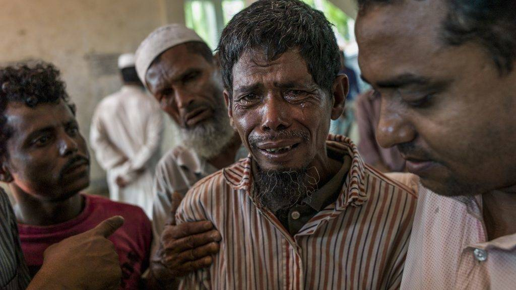 Rohingya Muslim refugee mourn beside bodies at a school near Inani beach in Cox's Bazar district on September 29, 2017. More than half a million Rohingya Muslims have poured into Bangladesh in the last month, fleeing a vicious Myanmar military crackdown on Rohingya rebels that has gutted villages across northern Rakhine state. Scores have drowned while trying to cross waters separating the two countries, while those who survive face new dangers as they cram into squalid refugee settlements where food and clean water are in short supply.  / AFP PHOTO / FRED DUFOUR