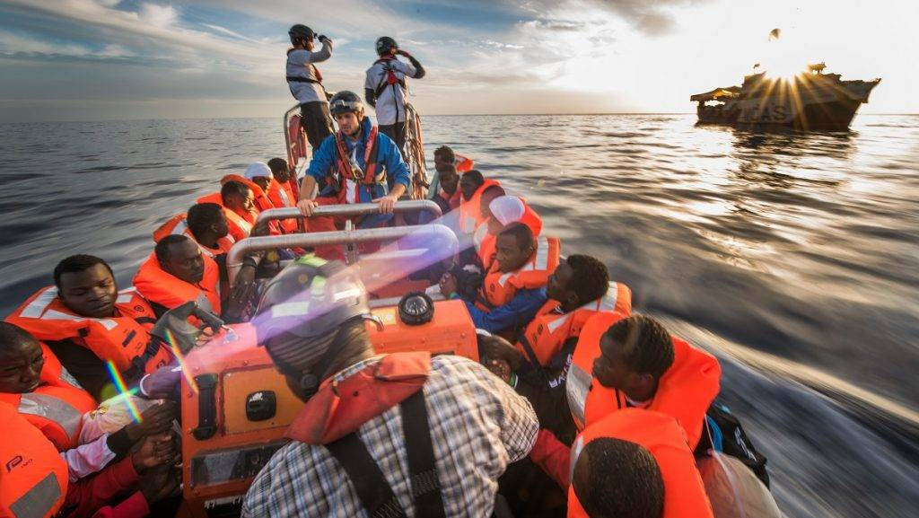 Refugees, who got rescued from distress at sea in international waters offshore the libyan coast in the mediterranean sea by the NGO SOS Mediterranee on 03 Dec 2016, get transferred on the MV Aquarius to the boat of the NGO MOAS. | usage worldwide
