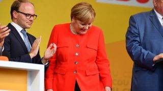 German Chancellor Angela Merkel looks at a stain on her jacket during a campaign event at the University Square in Heidelberg, Germany, 5 September 2017. A table in front of her was hit by an object thrown from the audience, resulting in a stain on Merkel's jacket. The chairman of the CDU Heidelberg, Alexander Foehr, stands left to her. Photo: Uwe Anspach/dpa