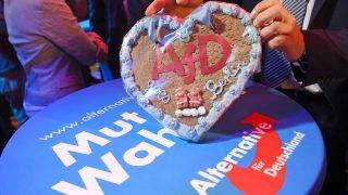 """A man holding a lebkuchen heart that reads """"AfD goes Berlin"""" at an Alternative fuer Deutschland (AfD, Alternative for Germany) election party in Berlin, Germany, 24 September 2017. Photo: Julian Stratenschulte/dpa"""