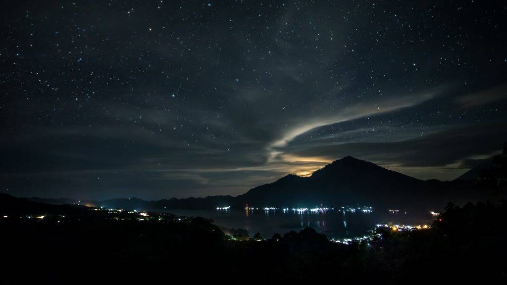 INDONESIA, BALI. THE SKY IS FULL OF STARS ABOVE THE BATUR LAKE AND THE AGUNG VOLCANO
