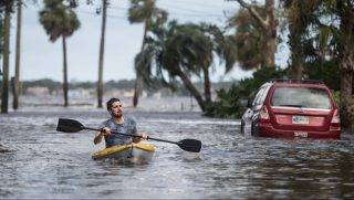 JACKSONVILLE, FL - SEPTEMBER 11: Justin Hand navigates storm surge flood waters from Hurricane Irma along the St. Johns River on Sept. 11, 2017 in Jacksonville, Florida. Flooding in downtown Jacksonville along the river topped a record set during Hurricane Dora in 1965.   Sean Rayford/Getty Images/AFP