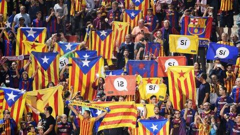 """Catalan football fans hold Esteladas and flag reading """"Yes"""" before the Spanish league football match Girona FC vs FC Barcelona at the Montilivi stadium in Girona on September 23, 2017.Spain's Prime Minister Mariano Rajoy asked Catalan separatist leaders today to own up they can't hold an outlawed independence referendum after a crackdown dealt them a serious blow this week. / AFP PHOTO / Josep LAGO"""