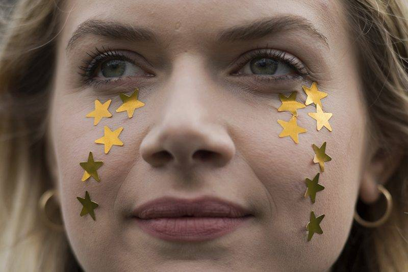 """A protester with 12 gold stars representing the European flag stars, as tears on her cheeks, takes part in a """"Flag Mob"""" in Parliament Square in central London on February 20, 2017, part of a national day of action in support of migrants in the UK. Under the banner 'One Day Without Us' men, women and children come together for a day of action to stress that they want Britain to remain open and welcoming. A number of businesses closed for the day to make the point that the Britain couldn't manage for even one day without the contribution of migrants.  / AFP PHOTO / Justin TALLIS"""