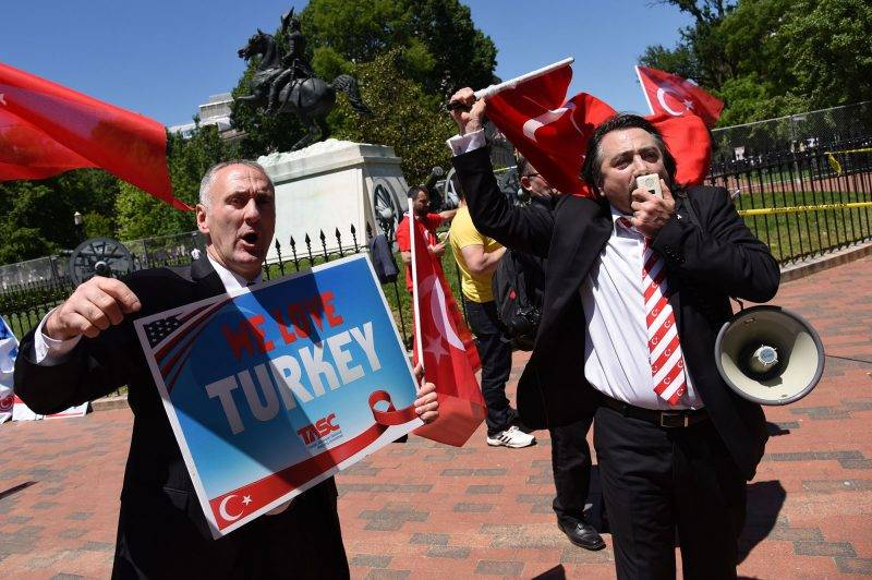 People wave Turkish flags and signs during a rally in front of the White House in Washington,DC on May 16, 2017.Presidents Donald Trump and Recep Tayyip Erdogan stood side by side at the White House on Tuesday and promised to work through strained ties despite the Turkish leader's stern warning about Washington's arming of a Kurdish militia. / AFP PHOTO / Olivier Douliery