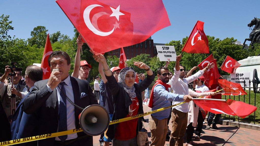 Pro-Erdogan supporters wave Turkish flags during a rally in front of the White House in Washington,DC on May 16, 2017.Presidents Donald Trump and Recep Tayyip Erdogan stood side by side at the White House on Tuesday and promised to work through strained ties despite the Turkish leader's stern warning about Washington's arming of a Kurdish militia. / AFP PHOTO / Olivier Douliery