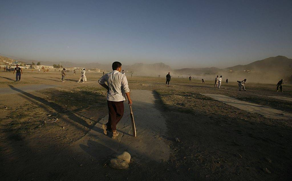 KABUL, AFGHANISTAN - JULY 27:  An Afghan cricket player waits on the pitch on a dusty field during a local league game July 27, 2007 in Kabul, Afghanistan. After the fall of the Taliban when the refugees returned from camps in Pakistan they came back having learned a new sport, Cricket. There are now leagues spread across the country playing in dusty fields. For the average Afghan team the equipment is cheap but the uniforms are not affordable so they play in sandals and their traditional shawal kamis. (Photo by Paula Bronstein/Getty Images)