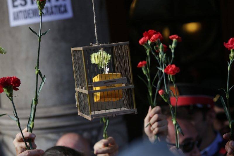 BARCELONA, SPAIN - SEPTEMBER 20 : Demonstrators hold clove flowers within a protest in front of the Economy headquarters of Catalonia's regional government in Barcelona, Spain on September 20, 2017, during a search by Spain's Guardia Civil police. Albert Llop / Anadolu Agency