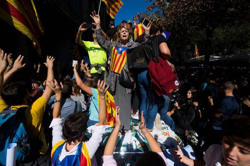BARCELONA, SPAIN - SEPTEMBER 20:  People demonstrate on a Spanish Civil Guard Police car outside the Catalan Vice-President and Economy office as police officers holds a searching operation inside on September 20, 2017 in Barcelona, Spain. Spanish Civil Guard police have stormed several Catalan government ministries in an attempt to stop the region's independence referendum on October 1, which has been deemed illegal by the Spanish government in Madrid.  (Photo by David Ramos/Getty Images)