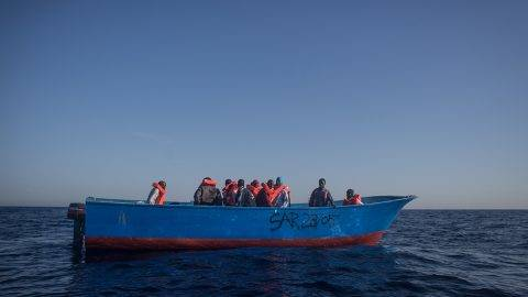 LAMPEDUSA, ITALY - JUNE 10:  Refugees and migrants wait in a small wooden boat to be rescued by crewmembers from the Migrant Offshore Aid Station (MOAS) Phoenix vessel on June 10, 2017 off Lampedusa, Italy. An estimated 230,000 refugees and migrants will arrive in Italy this year as numbers of refugees and migrants attempting the dangerous central Mediterranean crossing from Libya to Italy continues to rise since the same time last year. So far this year more than 58,000 people have arrived in Italy and 1,569 people have died attempting the crossing. Libya continues to be the primary departure point for refugees and migrants taking the central Mediterranean route to Sicily. In an attempt to slow the flow of migrants, Italy recently signed a deal with Libya, Chad and Niger outlining a plan to increase border controls and add new reception centers in the African nations, which are key transit points for migrants heading to Italy. MOAS is a Malta based NGO dedicated to providing professional search-and-rescue assistance to refugees and migrants in distress at sea. Since the start of the year MOAS have rescued and assisted more than 4000 people and are currently patrolling and running rescue operations in international waters off the coast of Libya.  (Photo by Chris McGrath/Getty Images)