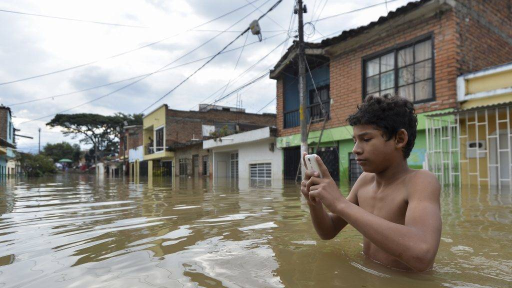 """A man checks his mobile phone in a flooded street in Cali, Colombia, on May 16, 2017, after heavy rains caused the overflowing of the Cauca river.  Colombia remains on """"alert"""" due to heavy rains which, since March, have left 389 people killed, some 23.000 families and over a third of the country affected. / AFP PHOTO / LUIS ROBAYO"""