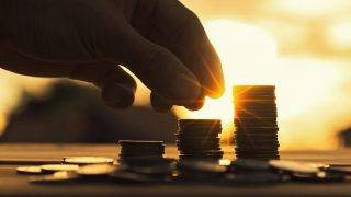 Saving money concept preset by Male hand putting money coin stack growing business. Close up of hand on sunset background, money concept, Business Finance and Money concept