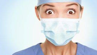 Doctor / surgeon shocked - funny. Woman closeup portrait of young doctor, surgeon or nurse surprised starring with big eyes wearing surgical mask. Asian / Caucasian female model.