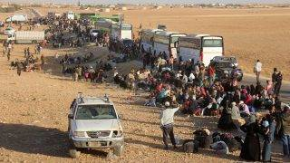 Syrian civilians and militants who were evacuated from northeastern Lebanon gather near buses after crossing into the rebel-held area of Al-Saan in the central Hama province on August 3, 2017.Nearly 8,000 Syrian refugees and fighters from Lebanon arrived in central Syria as part of a ceasefire deal that also saw five Hezbollah fighters released, a monitor and the Shiite militant group said / AFP PHOTO / Omar haj kadour
