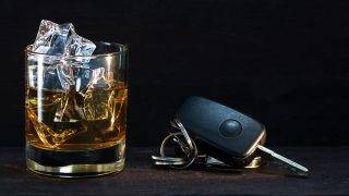Whiskey glass with ice and car keys on a rustic wooden table, dark background with copy space, concept alcohol and driving