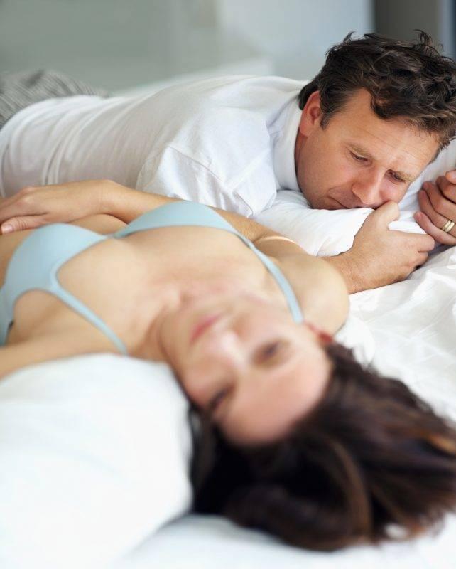 Handsome mature man sleeping besides wife on bed