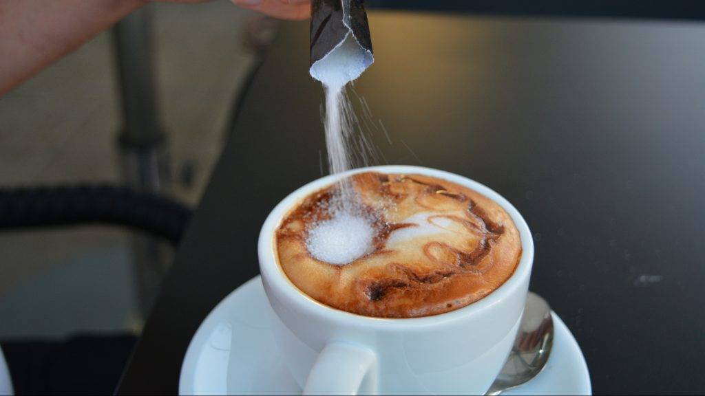 Man's hand pouring  sugar into white cup with cappuccino on black background